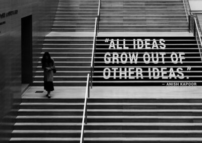 "A woman walking down a flight of stairs with a caption that reads, ""All ideas grow out of other ideas."" -Anish Kapoor"